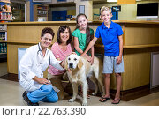 Купить «Woman vet and happy family smiling and posing with a dog», фото № 22763390, снято 17 января 2016 г. (c) Wavebreak Media / Фотобанк Лори