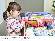 Маленькая девочка развешивает белье на сушилку. Стоковое фото, фотограф Анна Кирьякова / Фотобанк Лори