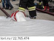 Пожарный наступил ногой на брандспойт, из которого вытекает пена. Стоковое фото, фотограф Маркин Роман / Фотобанк Лори