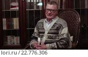 Купить «Веселый дед в очках вспоминает молодость на качалке возле книжного шкафа», видеоролик № 22776306, снято 11 марта 2016 г. (c) Video Kot / Фотобанк Лори
