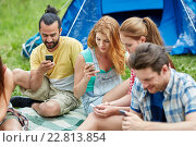 Купить «friends with smartphone and tent at camping», фото № 22813854, снято 18 июля 2019 г. (c) Syda Productions / Фотобанк Лори