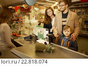 Купить «Young family in a grocery store», фото № 22818074, снято 9 октября 2015 г. (c) Andrejs Pidjass / Фотобанк Лори