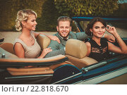 Купить «Wealthy friends in a classic convertible», фото № 22818670, снято 11 августа 2015 г. (c) Andrejs Pidjass / Фотобанк Лори