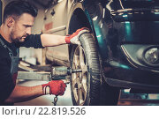 Купить «Professional car mechanic changing car wheel in auto repair service.», фото № 22819526, снято 26 февраля 2016 г. (c) Andrejs Pidjass / Фотобанк Лори