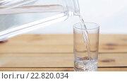 Купить «water pouring into glass on wooden table», видеоролик № 22820034, снято 2 апреля 2016 г. (c) Syda Productions / Фотобанк Лори
