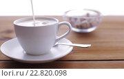Купить «cream pouring to coffee cup on wooden table», видеоролик № 22820098, снято 15 апреля 2016 г. (c) Syda Productions / Фотобанк Лори