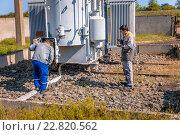 Рабочие электрики контролируют оборудование на подстанции высокого напряжения. Стоковое фото, фотограф Станислав Илюк / Фотобанк Лори