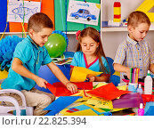Купить «Kids holding colored paper on table in kindergarten .», фото № 22825394, снято 4 октября 2015 г. (c) Gennadiy Poznyakov / Фотобанк Лори