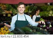 Купить «Market stuff offering slicing cucumbers», фото № 22833454, снято 18 января 2019 г. (c) Яков Филимонов / Фотобанк Лори