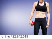 Купить «Composite image of sporty woman holding a red ball», фото № 22842518, снято 17 октября 2018 г. (c) Wavebreak Media / Фотобанк Лори