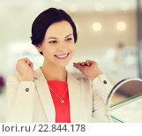 Купить «happy woman choosing pendant at jewelry store», фото № 22844178, снято 30 апреля 2015 г. (c) Syda Productions / Фотобанк Лори