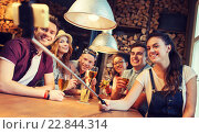 Купить «friends with smartphone on selfie stick at bar», фото № 22844314, снято 7 мая 2015 г. (c) Syda Productions / Фотобанк Лори