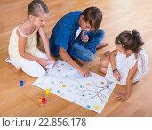 Купить «Boy and two girls playing at board game indoors», фото № 22856178, снято 16 августа 2018 г. (c) Яков Филимонов / Фотобанк Лори
