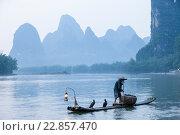 Старый рыбак закуривает трубку во время рыбалки традиционным для китая способом с помощью ручного баклана на фоне гор в провинции Гуанси (2013 год). Стоковое фото, фотограф Николай Винокуров / Фотобанк Лори