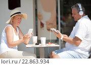 Светловолосая пожилая женщина в шляпе сидит за столом и использует мобильный телефон, а ее муж слушает музыку (2015 год). Редакционное фото, фотограф Данил Руденко / Фотобанк Лори