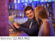 Купить «Молодая пара в баре. Мужчина листает меню, улыбается и смотри на девушку», фото № 22863962, снято 17 августа 2015 г. (c) Данил Руденко / Фотобанк Лори