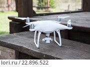 Купить «Белый квадрокоптер стоит на деревянном крыльце», фото № 22896522, снято 3 мая 2016 г. (c) Кекяляйнен Андрей / Фотобанк Лори