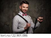 Купить «Stylish man with bow tie wearing suspenders and posing on dark background.», фото № 22901086, снято 11 апреля 2016 г. (c) Andrejs Pidjass / Фотобанк Лори