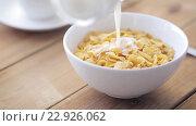 Купить «milk pouring to corn flakes on wooden table», видеоролик № 22926062, снято 15 апреля 2016 г. (c) Syda Productions / Фотобанк Лори