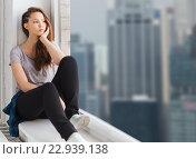 sad pretty teenage girl sitting on windowsill. Стоковое фото, фотограф Syda Productions / Фотобанк Лори
