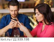 Купить «couple with smartphones dining at restaurant», фото № 22939198, снято 8 ноября 2015 г. (c) Syda Productions / Фотобанк Лори