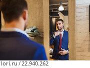 Купить «man trying tie on at mirror in clothing store», фото № 22940262, снято 1 апреля 2016 г. (c) Syda Productions / Фотобанк Лори