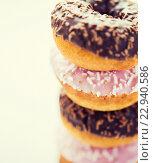 Купить «close up of glazed donuts pile over white», фото № 22940586, снято 21 мая 2015 г. (c) Syda Productions / Фотобанк Лори