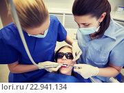 Купить «female dentists treating patient girl teeth», фото № 22941134, снято 23 мая 2015 г. (c) Syda Productions / Фотобанк Лори