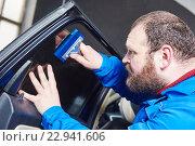 Купить «car tinting. Automobile mechanic technician applying foil», фото № 22941606, снято 14 апреля 2016 г. (c) Дмитрий Калиновский / Фотобанк Лори