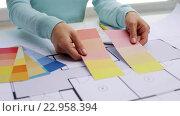Купить «woman with blueprint and swatches choosing color», видеоролик № 22958394, снято 14 мая 2016 г. (c) Syda Productions / Фотобанк Лори