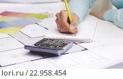 Купить «woman with blueprint counting on calculator», видеоролик № 22958454, снято 14 мая 2016 г. (c) Syda Productions / Фотобанк Лори