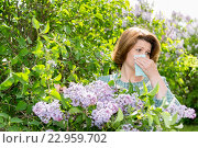 Woman suffering from pollen allergy about lilacs. Стоковое фото, фотограф Володина Ольга / Фотобанк Лори