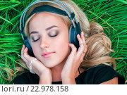 Блондинка в траве слушает музыку. Красивая молодая девушка с закрытыми глазами в наушниках. Стоковое фото, фотограф Евгений Пидеркин / Фотобанк Лори