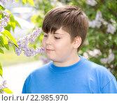 Купить «boy smelling a lilac flowers in park», фото № 22985970, снято 15 мая 2016 г. (c) Володина Ольга / Фотобанк Лори