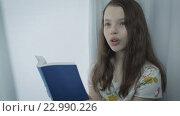 Купить «Красивая девочка учит стихотворение у окна», видеоролик № 22990226, снято 22 апреля 2016 г. (c) Юлия Машкова / Фотобанк Лори