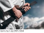Купить «Composite image of fighter tightening karate belt», фото № 22991554, снято 18 августа 2019 г. (c) Wavebreak Media / Фотобанк Лори
