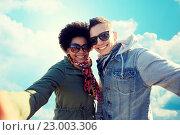 Купить «happy teenage couple taking selfie over blue sky», фото № 23003306, снято 19 марта 2015 г. (c) Syda Productions / Фотобанк Лори