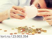 Купить «close up of man pouring coins from piggy bank», фото № 23003354, снято 18 июня 2015 г. (c) Syda Productions / Фотобанк Лори