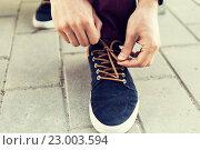 Купить «close up of male hands tying shoe laces on street», фото № 23003594, снято 30 мая 2015 г. (c) Syda Productions / Фотобанк Лори