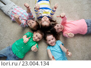 Купить «happy kids lying on floor and showing thumbs up», фото № 23004134, снято 31 января 2016 г. (c) Syda Productions / Фотобанк Лори