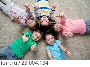 Купить «happy kids lying on floor and showing thumbs up», фото № 23004134, снято 31 января 2016 г. (c) Syda Productions / Фотобанк Лори