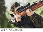 Купить «soldier or hunter shooting with gun in forest», фото № 23004186, снято 14 августа 2014 г. (c) Syda Productions / Фотобанк Лори