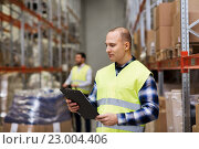 Купить «man with clipboard in safety vest at warehouse», фото № 23004406, снято 9 декабря 2015 г. (c) Syda Productions / Фотобанк Лори