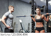 Купить «man and woman with barbell flexing muscles in gym», фото № 23004494, снято 19 апреля 2015 г. (c) Syda Productions / Фотобанк Лори