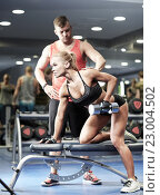 Купить «young couple with dumbbell flexing muscles in gym», фото № 23004502, снято 19 апреля 2015 г. (c) Syda Productions / Фотобанк Лори