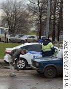Водитель автомобиля снимает государственный регистрационный знак за нарушение правил дорожного движения (2013 год). Редакционное фото, фотограф Free Wind / Фотобанк Лори