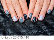 Купить «Women#39;s hands with a stylish manicure. On each nail lacquer struck with a different shade of gray. Background in the form of small squares quilted leather glossy textured fabric.», фото № 23015410, снято 17 августа 2018 г. (c) age Fotostock / Фотобанк Лори