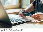 Купить «Руки с банковской картой над клавиатурой ноутбука», фото № 23029934, снято 3 мая 2016 г. (c) Константин Колосов / Фотобанк Лори