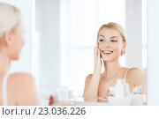 Купить «happy woman applying cream to face at bathroom», фото № 23036226, снято 13 февраля 2016 г. (c) Syda Productions / Фотобанк Лори