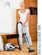 Купить «Housewife vacuuming floor and furniture», фото № 23037794, снято 17 августа 2018 г. (c) Яков Филимонов / Фотобанк Лори